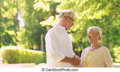 happy senior couple talking at summer city park - old age,...