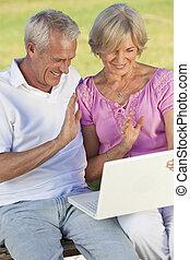 Happy Senior Couple Using Laptop Computer Outside in Sunshine