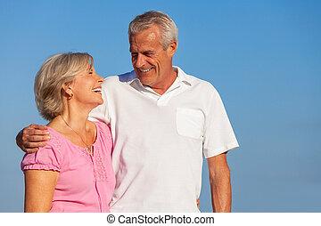 Happy Senior Couple Walking Embracing in Blue Sky