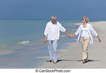 Happy Senior Couple Walking Holding Hands on Beach