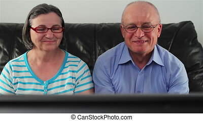 Happy senior couple watching television together
