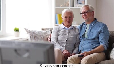 happy senior couple watching tv at home