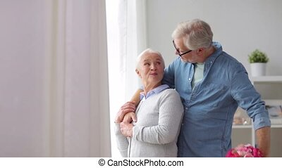 happy senior couple with bunch of flowers at home -...