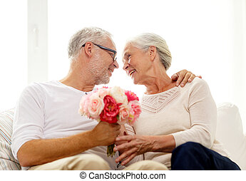 happy senior couple with bunch of flowers at home - family,...