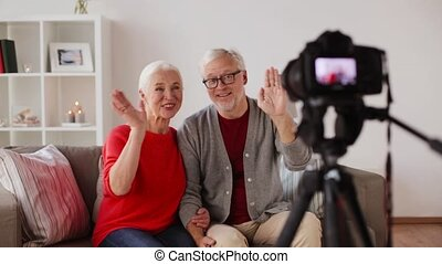 happy senior couple with camera recording video -...