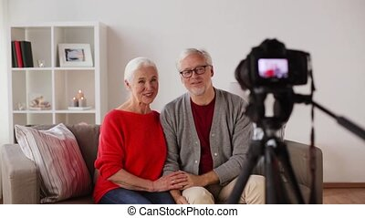 happy senior couple with camera recording video -...