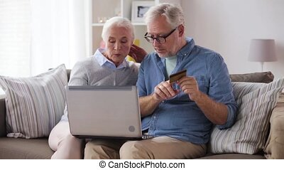 happy senior couple with laptop and credit card