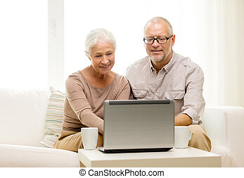 happy senior couple with laptop and cups at home - family,...