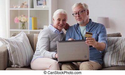 happy senior couple with laptop and credit card - family,...