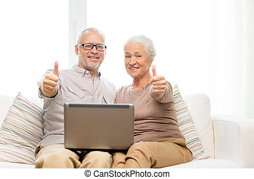 happy senior couple with laptop at home - family,...