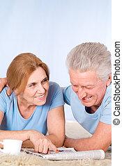 happy senior couple with newspaper