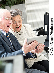happy senior couple with tablet computer