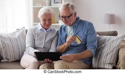 happy senior couple with tablet pc and credit card - family,...