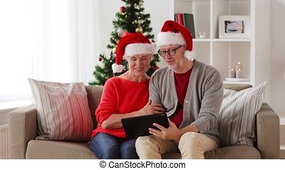 happy senior couple with tablet pc at christmas