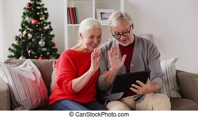 happy senior couple with tablet pc at christmas - christmas,...