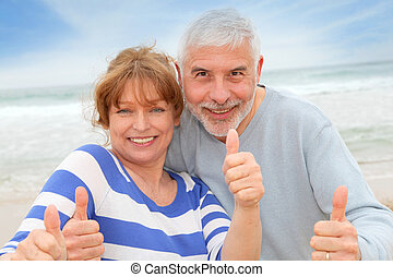 Happy senior couple with thumbs up at the beach