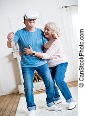 Happy senior couple with virtual reality headset having fun at home