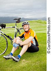 happy senior cyclist resting on grass