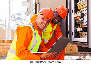happy senior electrical engineer with co-worker in substation