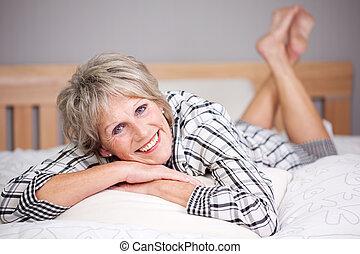 Happy senior female lying in bed inside the living room
