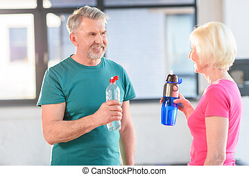 Happy senior fitness couple holding bottles with water gym
