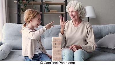 Happy senior grandma and granddaughter playing jenga game at home