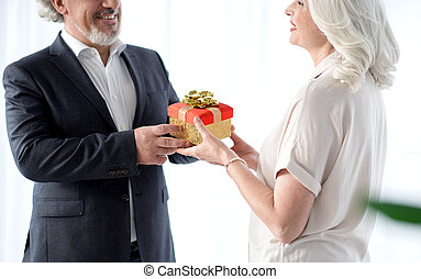 Happy senior husband handing over present to his wife - This...