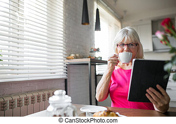 Happy senior lady drinking coffee using tablet at home