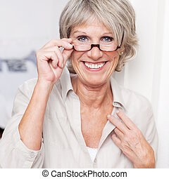 Happy senior lady wearing reading glasses