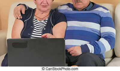 Happy senior man and a woman watching the movie on the laptop. They hug and discuss what is happening on the screen. Beautiful interior of the house