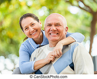 Happy senior man and mature woman against the park