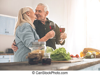 Happy senior man and woman drinking wine with romance