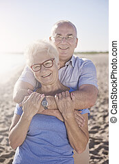 Happy senior man and woman on the beach