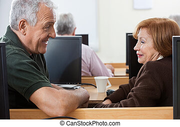 Happy Senior Man And Woman Sitting In Computer Class