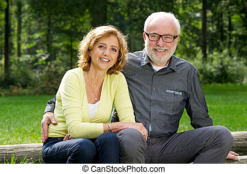Happy senior man and woman sitting together outdoors