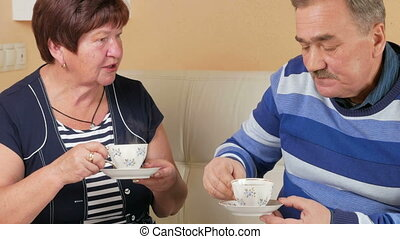 Happy senior man and woman talking at home over a cup of coffee. Husband and wife in a beautiful house to discuss the events of the day