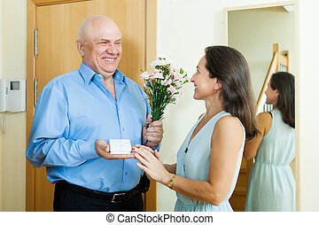 Happy senior man came to mature woman with present