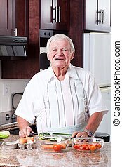 happy senior man cooking in kitchen