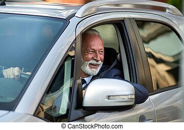 Happy senior man driving car