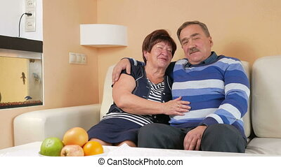 Happy senior man embracing his beloved wife on a sofa in a beautiful house. They talk and laugh. Looking at the camera with a smile