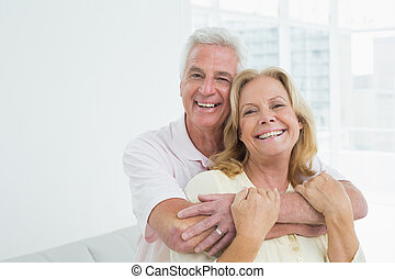 Happy senior man embracing woman from behind