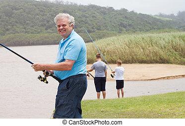 happy senior man fishing with grandsons