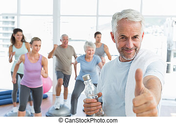 Happy senior man gesturing thumbs up with people exercising ...