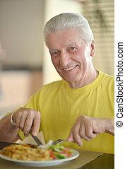 Happy Senior man having breakfast
