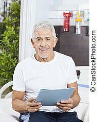 Happy Senior Man Holding Report At Rehab Center - Portrait...