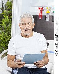 Happy Senior Man Holding Report At Rehab Center