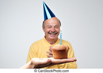 Happy senior man in birtyday hat is happpy to receive small cake with one candle