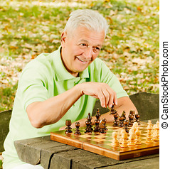 happy senior man playing chess on a park bench