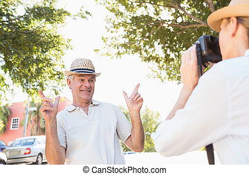 Happy senior man posing for his partner taking photo