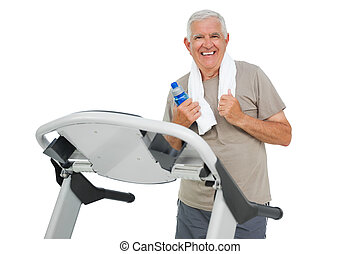 Happy senior man running on a treadmill